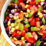 Black bean and corn salad in a white bowl on a napkin.