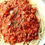 Slow Cooker Bolognese Sauce over spaghetti on plate.