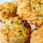 Cheddar Bay Biscuits stacked up on a plate.