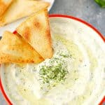 Overhead shot of tzatziki sauce in bowl, with pita chips dipped.