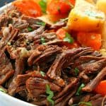 Pot roast with potatoes and carrots on plate.