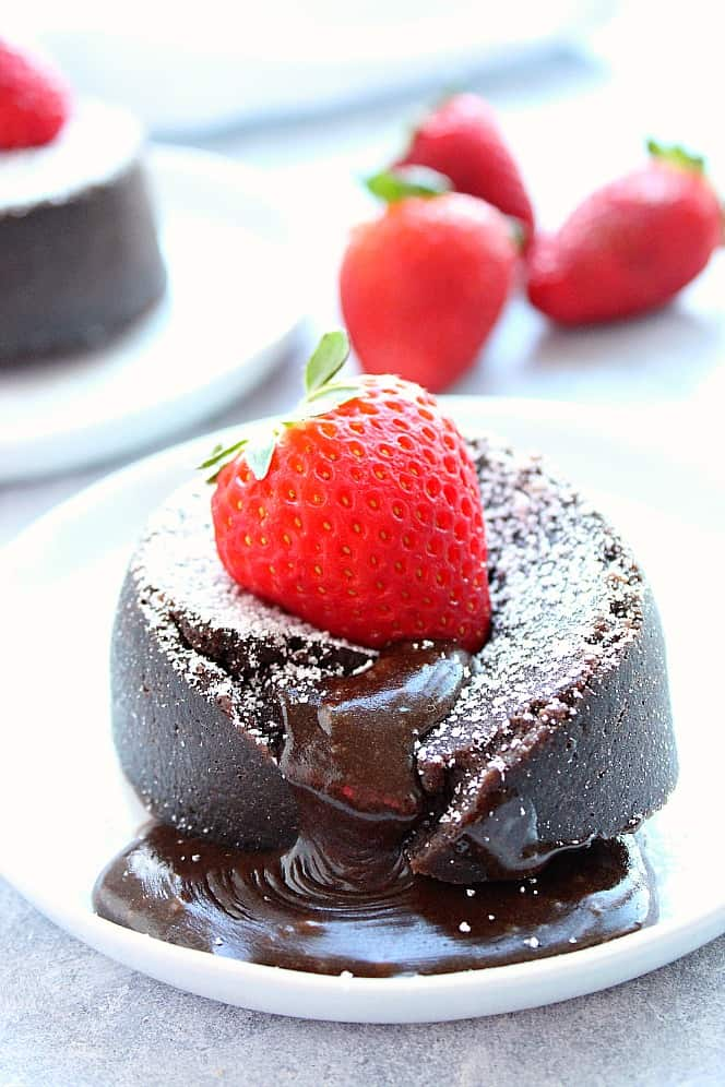 Instant Pot chocolate lava cake with strawberry on top on white plate. Instant Pot Chocolate Lava Cake For Two