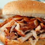 Instant Pot Pulled Pork in a bun on white plate.