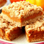 Pumpkin pie bars stacked on plate.